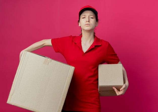 真っ赤な背景で隔離のカートンボックスを保持している赤い制服と帽子の不機嫌な若いかわいい配達の女の子