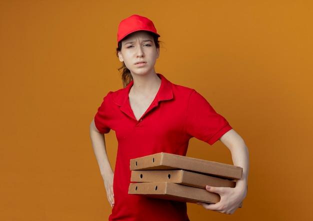 コピースペースとオレンジ色の背景で隔離の腰に手を置いてピザパッケージを保持している赤い制服と帽子の不幸な若いかわいい配達の女の子