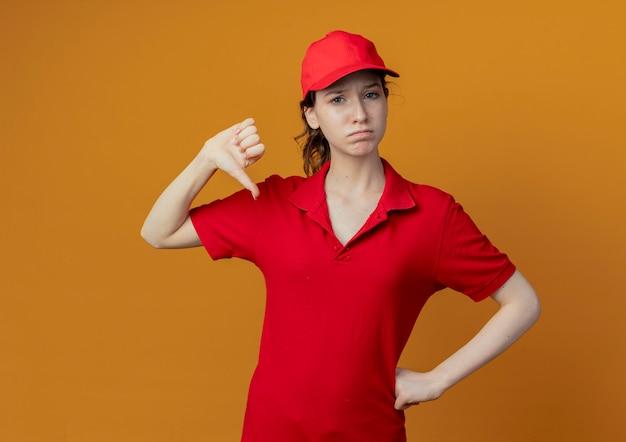 赤い制服とキャップで腰に手を置き、コピースペースでオレンジ色の背景に分離された親指を下に見せて不機嫌な若いかわいい配達の女の子
