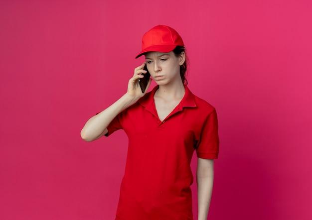 Недовольная молодая симпатичная доставщица в красной форме и кепке разговаривает по телефону, глядя вниз на малиновом фоне с копией пространства