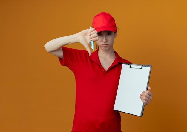 Giovane ragazza graziosa di consegna poco soddisfatta in uniforme rossa e cappuccio che tengono penna e appunti che mostrano il pollice giù isolato su fondo arancio con lo spazio della copia