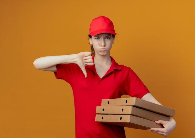 Giovane ragazza graziosa di consegna poco soddisfatta in uniforme rossa e cappuccio che tiene i pacchetti della pizza e che mostra il pollice giù isolato su fondo arancio