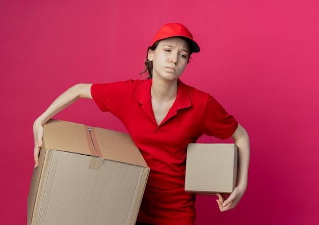 Giovane ragazza graziosa di consegna dispiaciuta in uniforme rossa e cappuccio che esamina il lato e che tiene le scatole di cartone