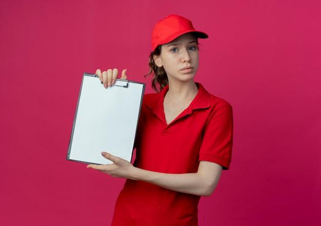 Giovane ragazza graziosa di consegna poco soddisfatta in uniforme rossa e cappuccio che mostra appunti isolati su fondo cremisi con lo spazio della copia
