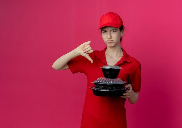 赤い制服を着て、食品容器を保持し、コピースペースで深紅色の背景に分離された親指を下に見せてキャップを身に着けている不機嫌な若いかわいい配達の女の子