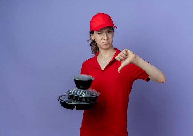 赤い制服を着て、食品容器を保持し、コピースペースで紫色の背景に分離された親指を下に見せてキャップを身に着けている不機嫌な若いかわいい配達の女の子