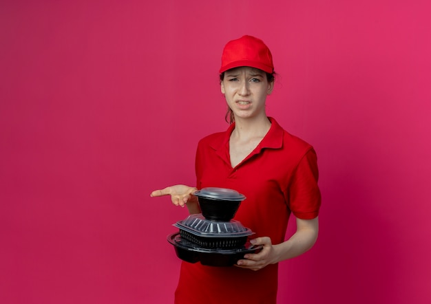 Unpleased young pretty delivery girl wearing red uniform and cap holding and pointing with hand at food containers isolated on crimson background with copy space
