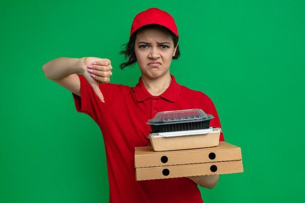 Una giovane e graziosa donna delle consegne scontenta che tiene in mano contenitori per alimenti con imballaggi su scatole per pizza e fa il pollice verso il basso