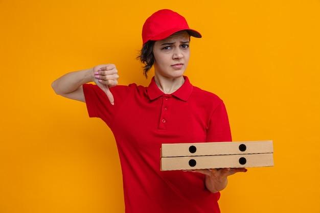 Una giovane e graziosa donna delle consegne scontenta che tiene in mano scatole di pizza e fa il pollice verso il basso