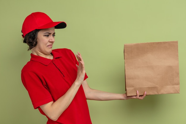 Unpleased young pretty delivery woman holds and looks at paper food packaging