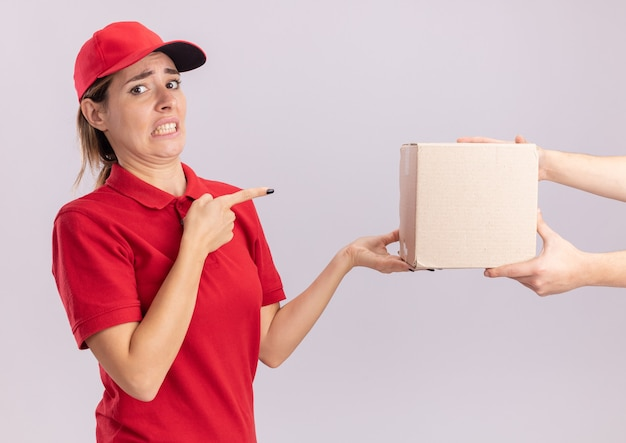 制服を着た不機嫌な若いかわいい配達の女性は、白い壁に隔離された誰かとポイントにカードボックスを与えます