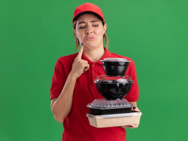 La giovane donna graziosa di consegna dispiaciuta in uniforme tiene e guarda i contenitori per alimenti sulla confezione per alimenti isolata