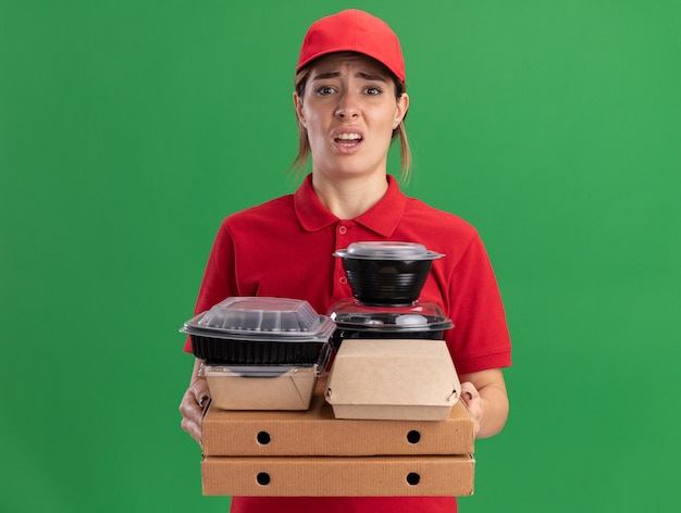 La giovane donna graziosa di consegna insoddisfatta in uniforme tiene i pacchetti e i contenitori di cibo di carta sulle scatole della pizza isolate sulla parete verde