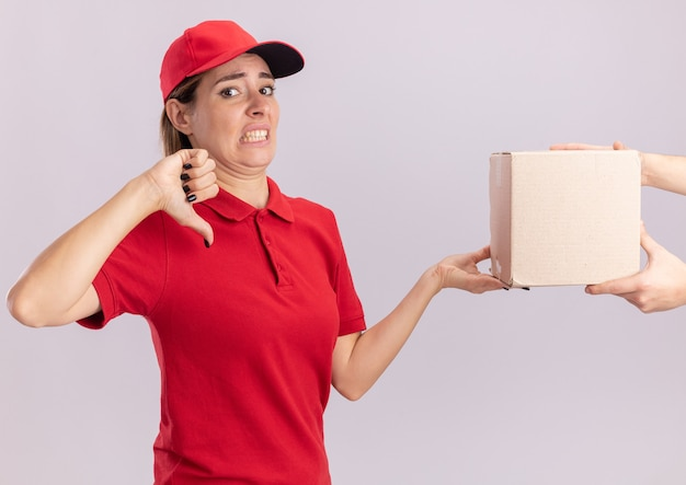 Unpleased young pretty delivery woman in uniform thumbs down and gives cardbox to someone isolated