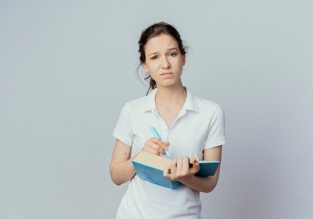 Studentessa graziosa giovane insoddisfatta che tiene libro aperto e penna isolato su priorità bassa bianca con lo spazio della copia