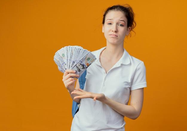 Недовольная молодая симпатичная студентка в задней сумке, держащая и указывающая рукой на деньги, изолированные на оранжевом фоне с копией пространства