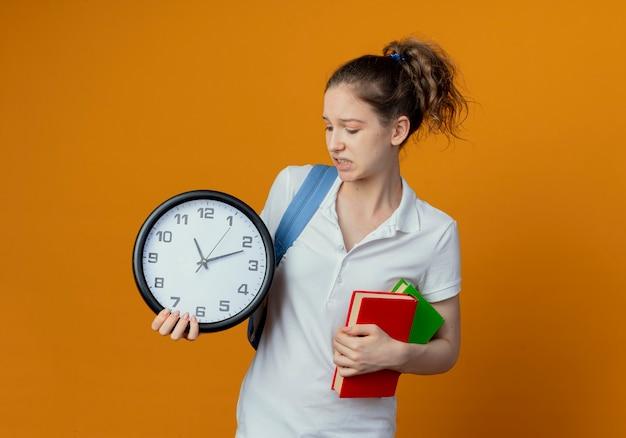 Giovane studentessa graziosa dispiaciuta che indossa la borsa posteriore che tiene e che guarda l'orologio e che tiene i libri isolati su fondo con lo spazio della copia