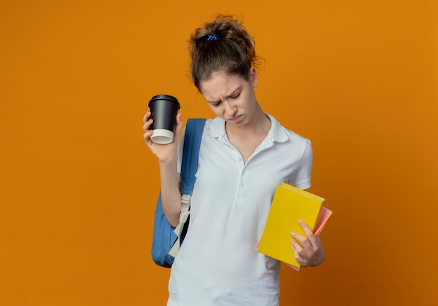 コピースペースでオレンジ色の背景に分離された本のメモ帳ペンとプラスチック製のコーヒーカップを保持して見下ろしているバックバッグを身に着けている不機嫌な若いきれいな女性