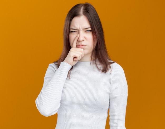 オレンジ色の壁に隔離された鼻に指を置く不機嫌な若いかわいい女の子