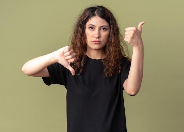 Una giovane ragazza carina scontenta che mostra i pollici su e giù isolata sul muro verde oliva