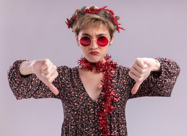 크리스마스 머리 화 환을 착용 하 고 흰색 벽에 고립 된 아래로 엄지 손가락을 보여주는 안경 목 주위에 반짝이 화 환을 착용하는 불쾌 하 게 젊은 예쁜 여자