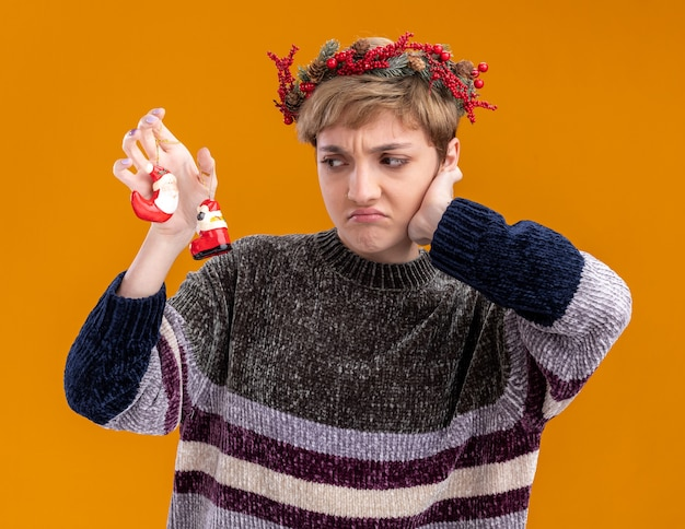 Unpleased young pretty girl wearing christmas head wreath holding and looking at santa claus christmas ornaments keeping hand on face isolated on orange wall