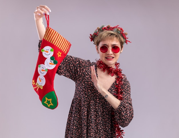 Unpleased young pretty girl wearing christmas head wreath and tinsel garland around neck with glasses holding christmas stocking looking at it doing refusal gesture isolated on white wall with copy space