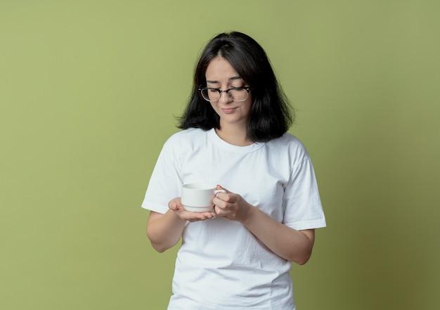 眼鏡をかけてカップを持って見ている不機嫌な若いかわいい女の子