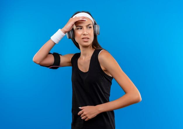 Giovane ragazza abbastanza sportiva dispiaciuta che indossa la fascia e il braccialetto e le cuffie con la fascia del telefono che mette la mano sulla fronte e che esamina il lato isolato sullo spazio blu