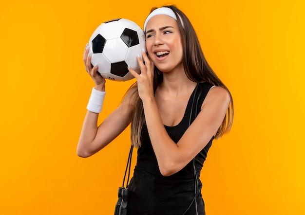 Giovane ragazza abbastanza sportiva dispiaciuta che indossa la fascia e il braccialetto che tiene il pallone da calcio che guarda al lato con la corda di salto intorno al suo collo isolato sullo spazio arancione