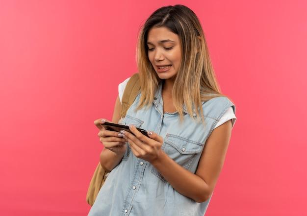 Ragazza giovane e graziosa studentessa dispiaciuta che indossa la borsa posteriore che tiene e che esamina il telefono cellulare isolato su fondo rosa con lo spazio della copia