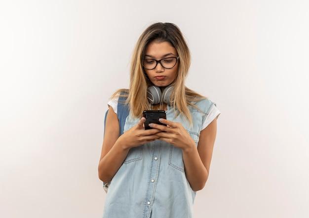 コピースペースと白い背景で隔離の彼女の携帯電話を使用して首にヘッドフォンとメガネとバックバッグを身に着けている不機嫌な若いかわいい学生の女の子