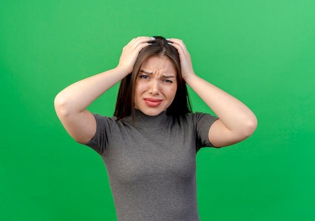 緑の背景で隔離の彼女の頭を保持している不機嫌な若いきれいな女性