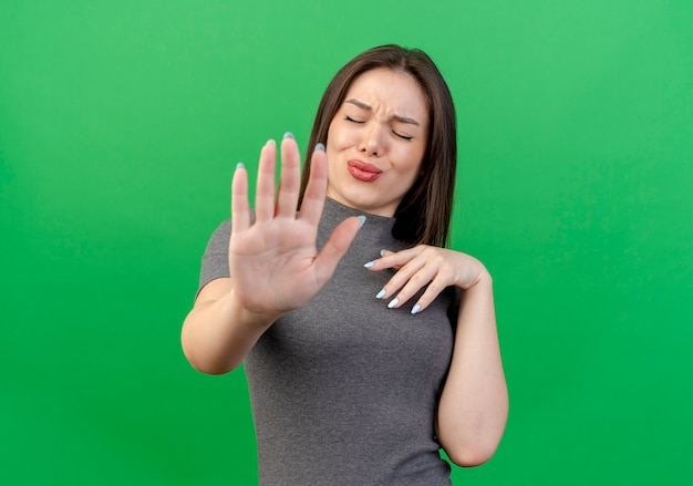 Giovane donna graziosa dispiaciuta mantenendo la mano sul petto e gesticolando fermata alla macchina fotografica con gli occhi chiusi isolato su sfondo verde con spazio di copia