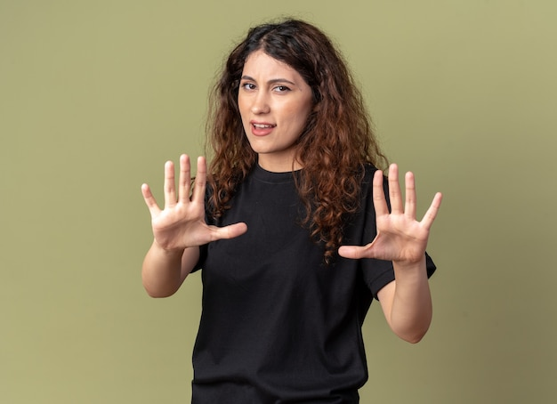 Unpleased young pretty woman looking at front doing stop gesture isolated on olive green wall with copy space