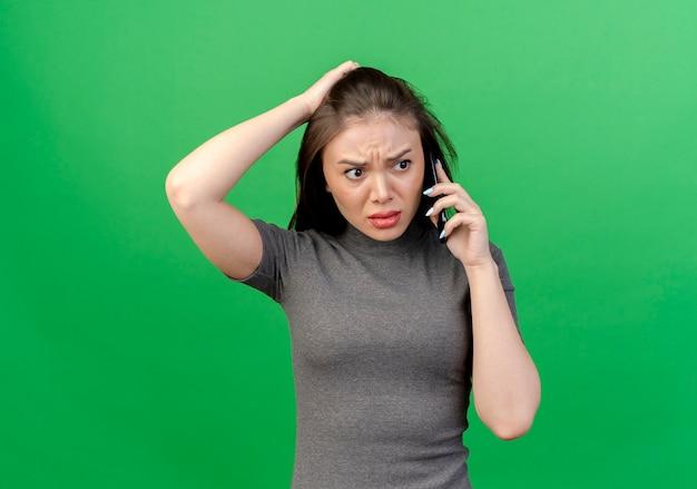 コピースペースと緑の背景で隔離の頭に手を置く側を見て電話で話している不機嫌な若いきれいな女性