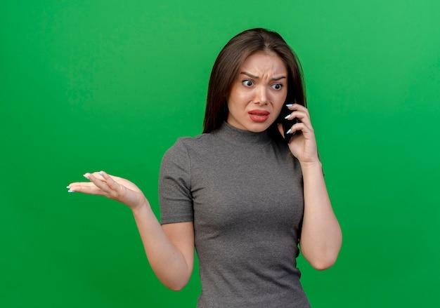 복사 공간 녹색 배경에 고립 된 빈 손을 보여주는 똑바로보고 전화로 얘기 불쾌 젊은 예쁜 여자