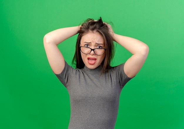 緑の背景で隔離の頭に手を置いて眼鏡をかけている不機嫌な若いきれいな女性