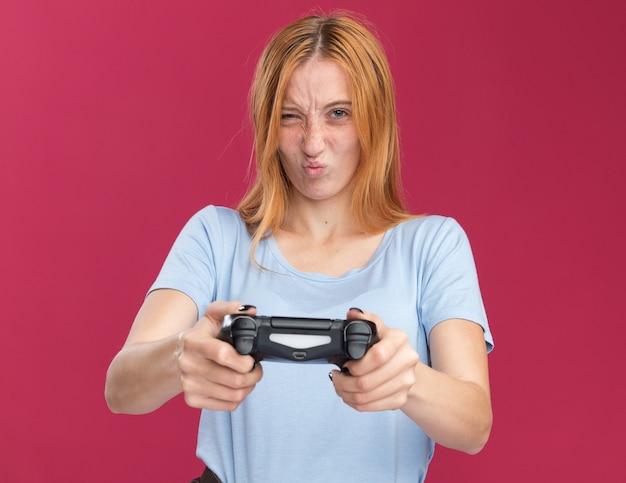 Недовольная рыжая рыжая девушка с веснушками держит игровой контроллер