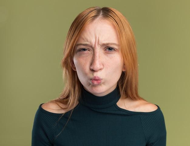 オリーブグリーンのカメラを見てそばかすと不機嫌な若い赤毛生姜の女の子