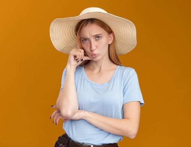 La giovane ragazza rossa scontenta dello zenzero con le lentiggini che indossa il cappello da spiaggia mette la mano sul tempio isolato sulla parete arancione con lo spazio della copia