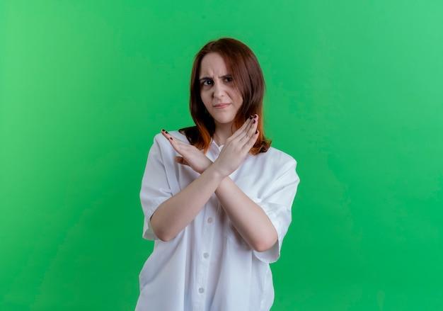 Недовольная молодая рыжая девушка, показывающая жест не изолирована на зеленой стене