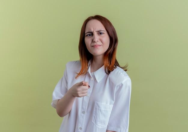 Giovane ragazza spiacevole della testarossa che ti mostra il gesto su verde oliva