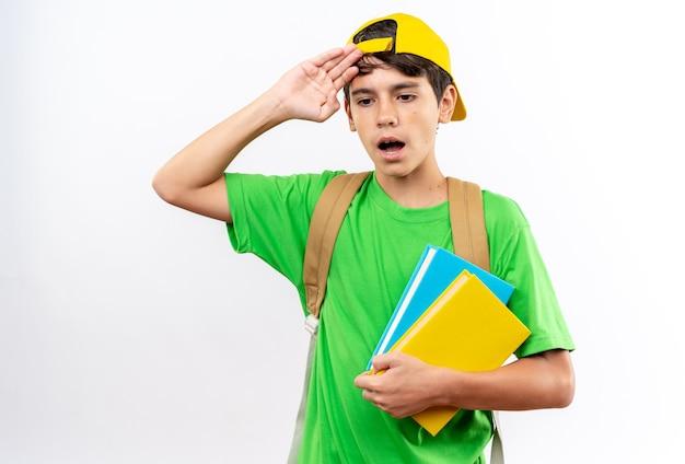 頭に手を置いて本を保持しているキャップ付きのバックパックを身に着けている不機嫌な少年