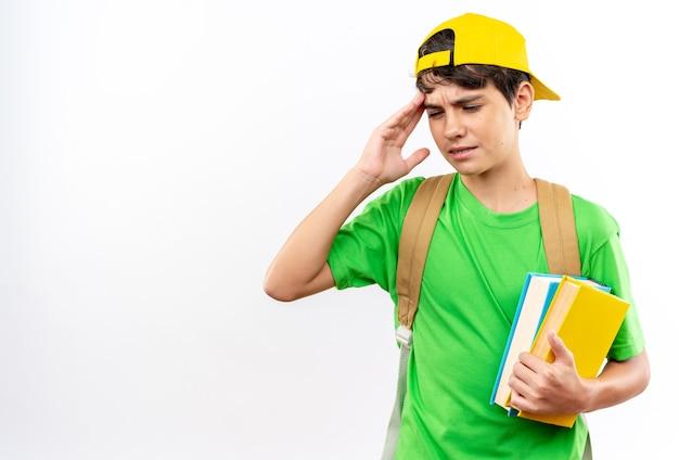 寺院に手を置く本を保持しているキャップ付きのバックパックを身に着けている不機嫌な少年