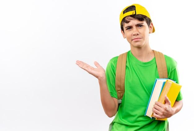Un giovane ragazzo di scuola scontento che indossa uno zaino con un cappello che tiene in mano i libri che spalmano la mano