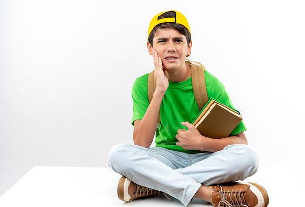 キャップ付きのバックパックを身に着けている不機嫌な少年は、本を持って頬に手を置いて床に座っています