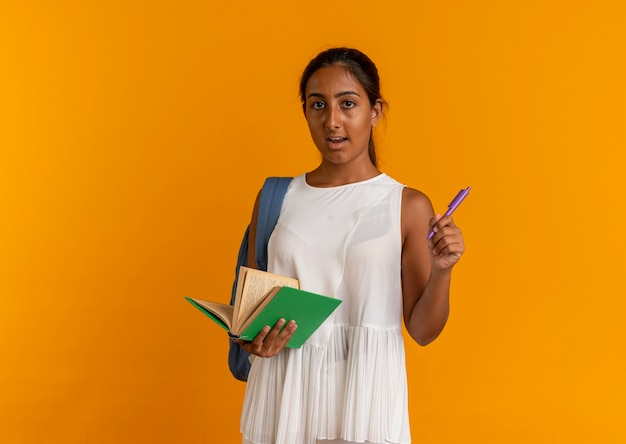 오렌지에 책과 펜을 들고 다시 가방을 입고 불쾌한 어린 여학생