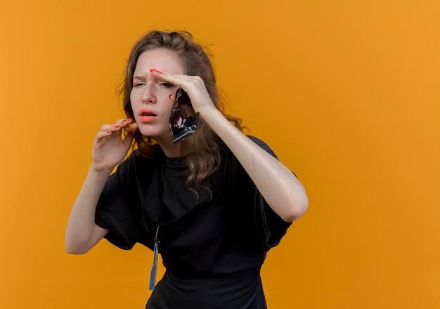 얼굴 근처에 손을 유지하는 머리 가위를 들고 똑바로 보이는 유니폼을 입고 불쾌한 젊은 슬라브 여성 이발사