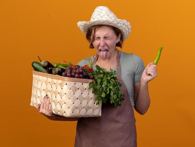 Il giovane giardiniere femminile slavo dispiaciuto che porta il cappello di giardinaggio sporge fuori la lingua che tiene il cestino della verdura e il peperoncino sull'arancia